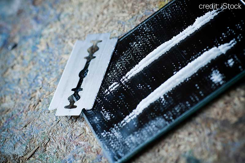 lines of cocaine on a mirror alongside a razor blade