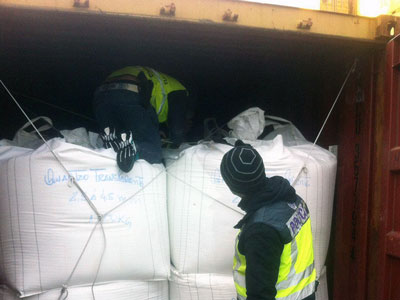 Spanish Police inspecting cocaine find within shipping container