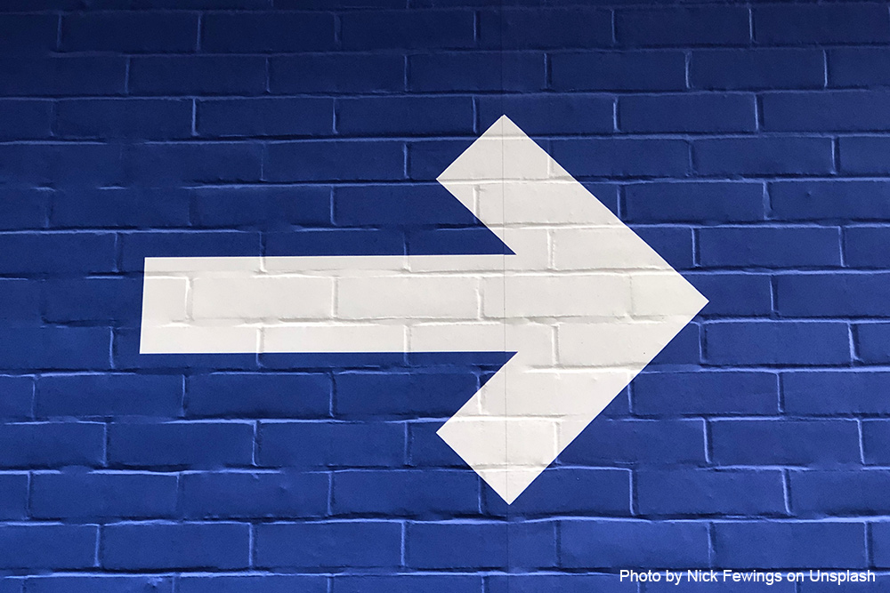 White arrow pointing to the right on blue brick wall