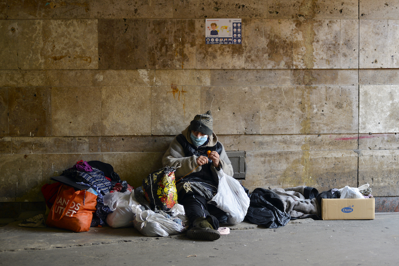 homeless woman in medical mask sits in an underground passage