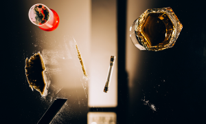 View through a glass table with a glass of alcohol, powder and a syringe