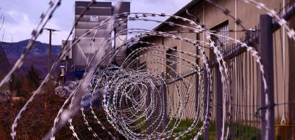 Picture shows outside of prision with razor wire.