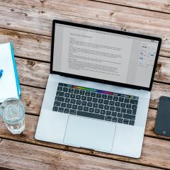 photo of laptop next to glass of water, notebook, a pen and mobile phone on wood table