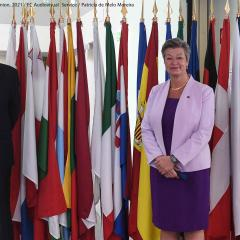 EMCDDA Director Alexis Goosdeel welcomes European Commissioner for Home Affairs Ylva Johansson posing for photographs in front of flags at the entrance of the EMCDDA in Lisbon