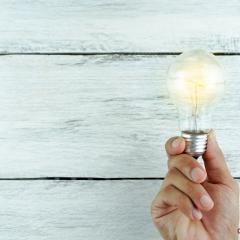 hand holding light bulb on a white wooden background
