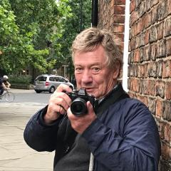 Picutre of Richard Hartnoll leaning against a brick wall. holding a camera, with trees in the background