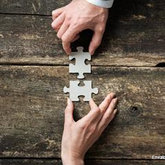 2 hands joining 2 jigsaw pieces
