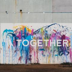 concrete wall with splashes of different colours with word together