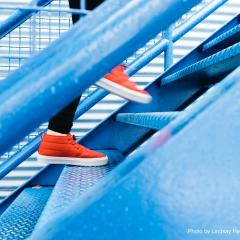 picture of someone in bright red running shoes climbing stairs