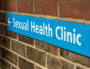 Blue sign on brick wall indication the direction to a Sexual Health Clinic