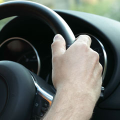 Hand on steering wheel driving a car
